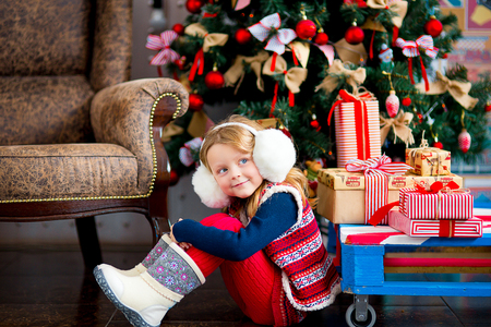 sweater girl: the girl in white fur earphones and red stockings sits near gifts and a Christmas fir-tree in red tones