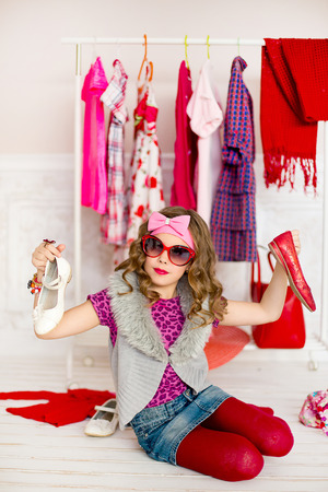 tries: the little girl in red sunglasses tries on leather shoes near a mobile hanger with clothes Stock Photo