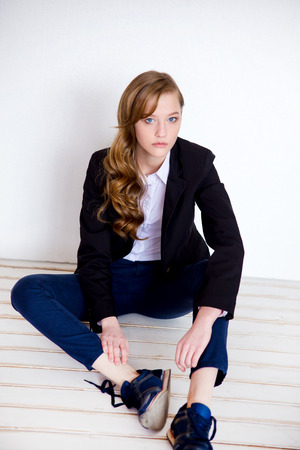 flashlights: the girl in a black jacket, a white shirt and blue jeans poses on a beige background with flashlights