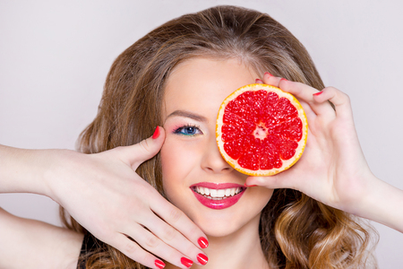 the girls portrait with a smile upon the face, a magnificent hairdress, red lips and nails with grapefruit. Advertizing of cosmetics and healthy lifestyle