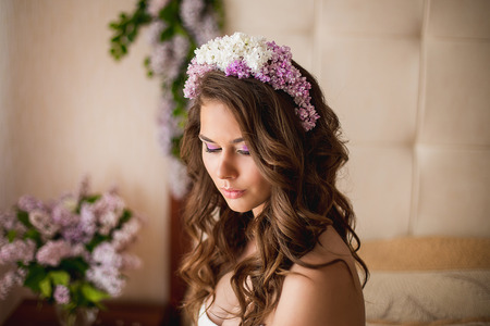 lilac: the bride in a wreath from a lilac lies on a bed, and nearby lilac flowers