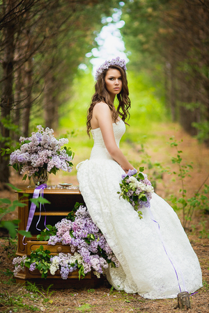 woman outdoor: the bride poses in the wood near a case with a lilac
