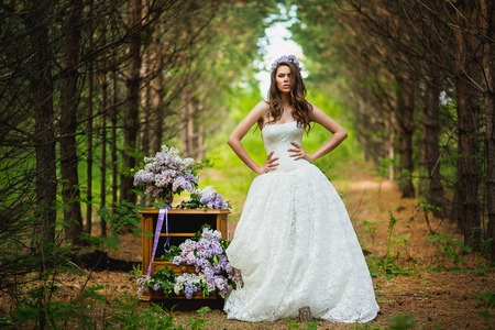the bride poses in the wood near a case with a lilac