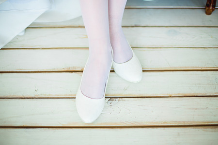 timber floor: feet in white shoes and white stockings stand on a white timber floor