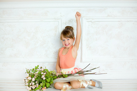 rejoices: the little girl disguised as the ballerina sits on a timber floor with a bouquet of flowers and rejoices