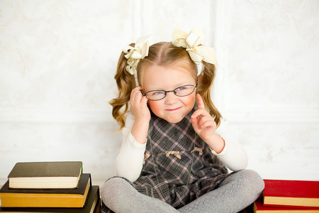 nice girl: education and school concept - smiling little student girl wearing spectacles with many books at school. The girl shakes finger