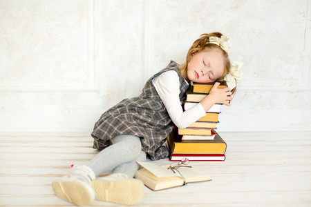 cute girl: education and school concept - smiling little student girl wearing spectacles with many books at school. The girl sleeps on books