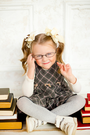 girl studying: education and school concept - smiling little student girl wearing spectacles with many books at school. The girl shakes finger