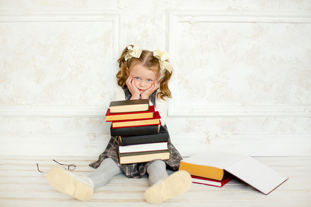 wearing spectacles: education and school concept - smiling little student girl wearing spectacles with many books at school Stock Photo