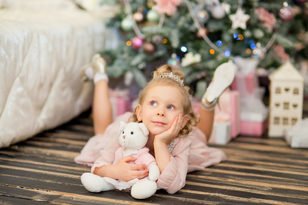 corona navidad: the little girl with white hair and a silver crown lies on a timber floor with a teddy bear near a Christmas fir-tree