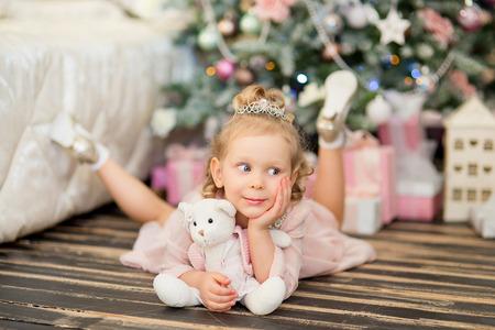 christmas crown: la ni�a con el pelo blanco y una corona de plata se encuentra en un piso de madera con un osito de peluche cerca de un abeto de Navidad