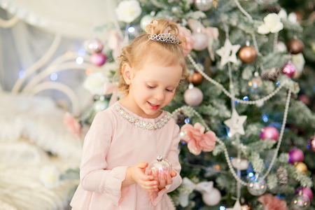 christmas crown: the little girl with white hair and a silver crown holds a New Years toy near a Christmas fir-tree