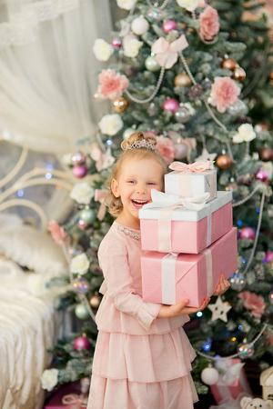 corona navidad: la niña con el pelo blanco y una corona de plata se levantó con regalos cerca de un abeto de Navidad también se ríe Foto de archivo