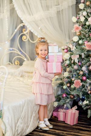 christmas crown: la ni�a con el pelo blanco y una corona de plata se levant� con los regalos acerca a un abeto de Navidad