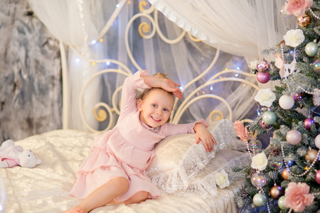 christmas crown: the little girl in a pink dress and a silver crown lies on a bed and smile near a Christmas fir-tree