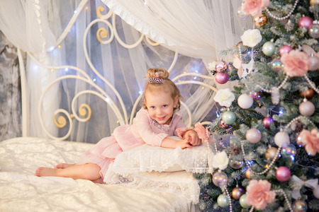 corona navidad: la ni�a en un vestido rosa y una corona de plata se encuentra en una cama y una sonrisa cerca de un abeto de Navidad Foto de archivo