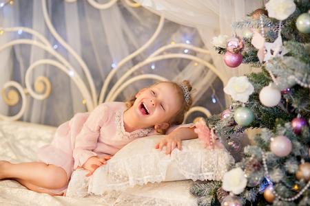 corona navidad: la niña en un vestido rosa y una corona de plata se encuentra en una cama y se ríe cerca de un abeto de Navidad Foto de archivo