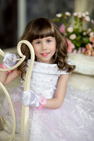 angel roses: the little girl with dark hair in an evening dress and in silk gloves poses on the forged bed Stock Photo