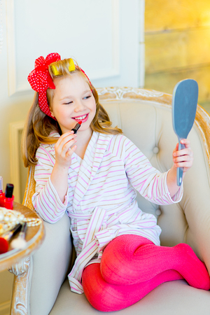 little table: the little girl in pin up style in a striped terry dressing gown, in hair curlers and with a red bandage in peas looks in a pocket mirror and makes up lips sitting in a chair near a little table with cosmetics
