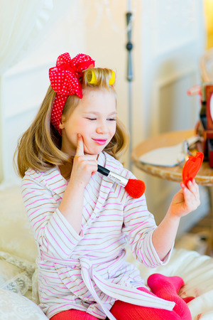 glamour makeup: the little girl in pin up style in a striped terry dressing gown, in hair curlers and with a red bandage in peas looks in a small pocket mirror with a red brush for powder Stock Photo