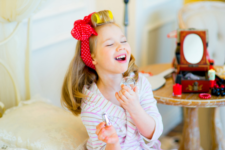 the little girl poses in pin up style in a striped terry dressing gown, in hair curlers and with a red bandage in peas, with a bottle of perfume in hands