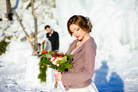 terrific: the bride with a bouquet of red flowers costs in the winter near a holiday table with cake. On background ice floe