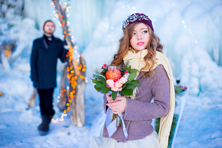 winter flower: the bride with a bouquet of red flowers costs in the winter near a holiday table with cake. On background ice floe