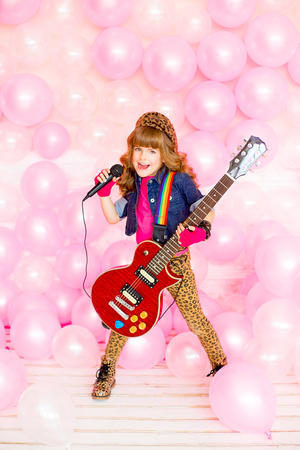 pink balloons: little girl singing a song with a microphone and a guitar on a background of pink balloons