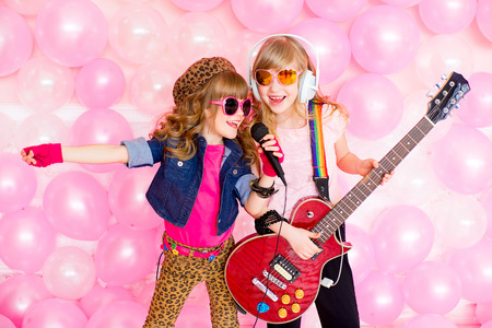 gente cantando: dos ni�a cantando una canci�n con un micr�fono y una guitarra sobre un fondo de globos de color rosa