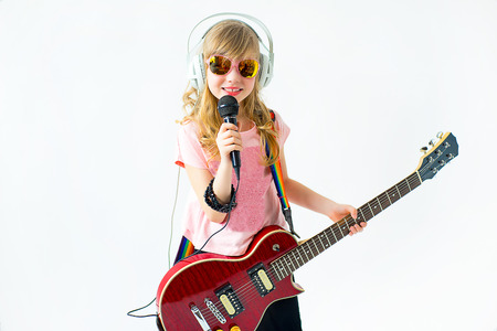 little girl singing a song with a microphone and a guitar on a white background. Isolate Foto de archivo