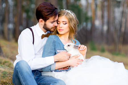 wedding, country-style glamor in the forest. Newlyweds posing among pine trees with white fluffy rabbits