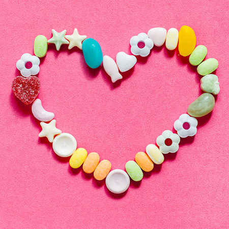 heart inlaid with colored candies of different shapes on a pink piece of paper Stock Photo