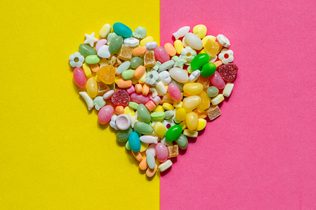 heart inlaid with colored candies of different shapes on a pink and yellow piece of paper