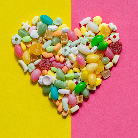 inlaid: heart inlaid with colored candies of different shapes on a pink and yellow piece of paper