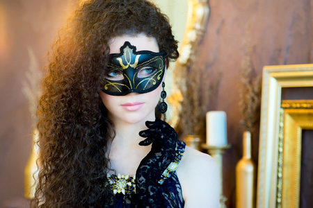 to conceal: woman with black curly hair and a masquerade mask posing on a brown background