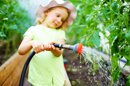 many babies: Gardening - little girl taking care of the plants in the greenhouse in the garden. Stock Photo
