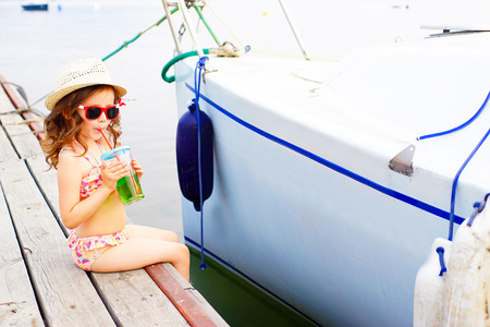 a bathing place: little girl in red sunglasses and bathing suit drinking sparkling water on the pier at the lake