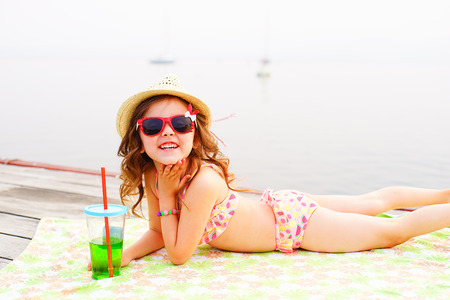 a bathing place: little girl in red sunglasses and bathing suit with sparkling water laughing at the pier near the lake