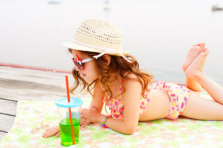 little girl in red sunglasses and bathing suit with sparkling water sunning at the pier at the lake