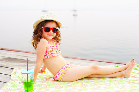 a bathing place: little girl in red sunglasses and bathing suit with sparkling water sunning at the pier at the lake