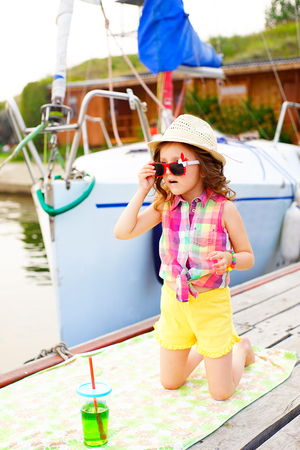 a bathing place: little girl in red sunglasses and bathing suit with sparkling water looks into the distance on a pier near the lake