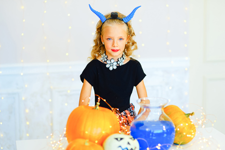 Little girl in demon costume during Halloween party playing around the table with pumpkins and bottle of potion