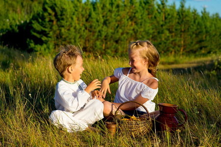 brother and sister on picnic sitting on green grass, warm summer vacations close up