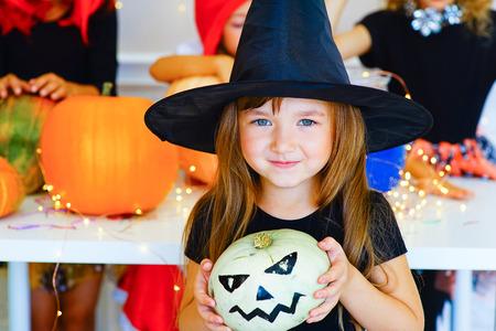 pocima: Feliz grupo de niños con trajes durante la fiesta de Halloween jugando alrededor de la mesa con las calabazas y botella de poción