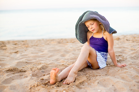 Little girl in a hat with a wide brim on the seashore posing and look around