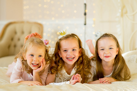 three little princess on the bed in classic dress and vintage atmosphere of the room