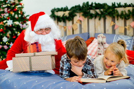 Santa Claus quietly came to the children who are reading a book while lying on decorated bed with Christmas tree in the background Stock Photo