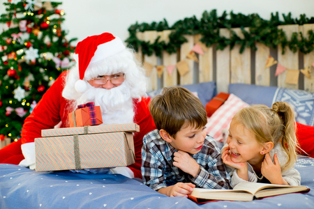 sneaks: Santa Claus quietly came to the children who are reading a book while lying on decorated bed with Christmas tree in the background Stock Photo