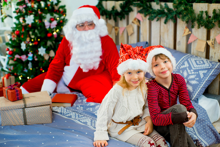 decide: Santa Claus and two children sitting on the bed looking at gifts decorated decide that open