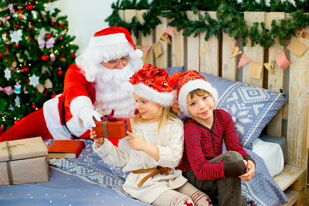 Santa Claus and two children sitting on the bed looking at gifts decorated decide that open